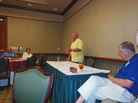 Bill Heath speaks; Bob Dorrill (foreground) and others listen.