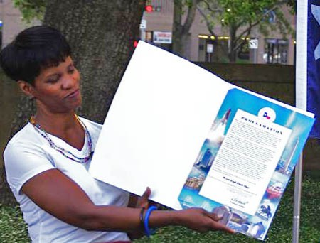 """Debra Sloan of the Harris County Historical Commission displays the City of Houston Proclamation that July 12, 2014 has been dubbed as """"West End Park Day"""" in Houston. ~ (Photo by Matt Rejmaniak)."""